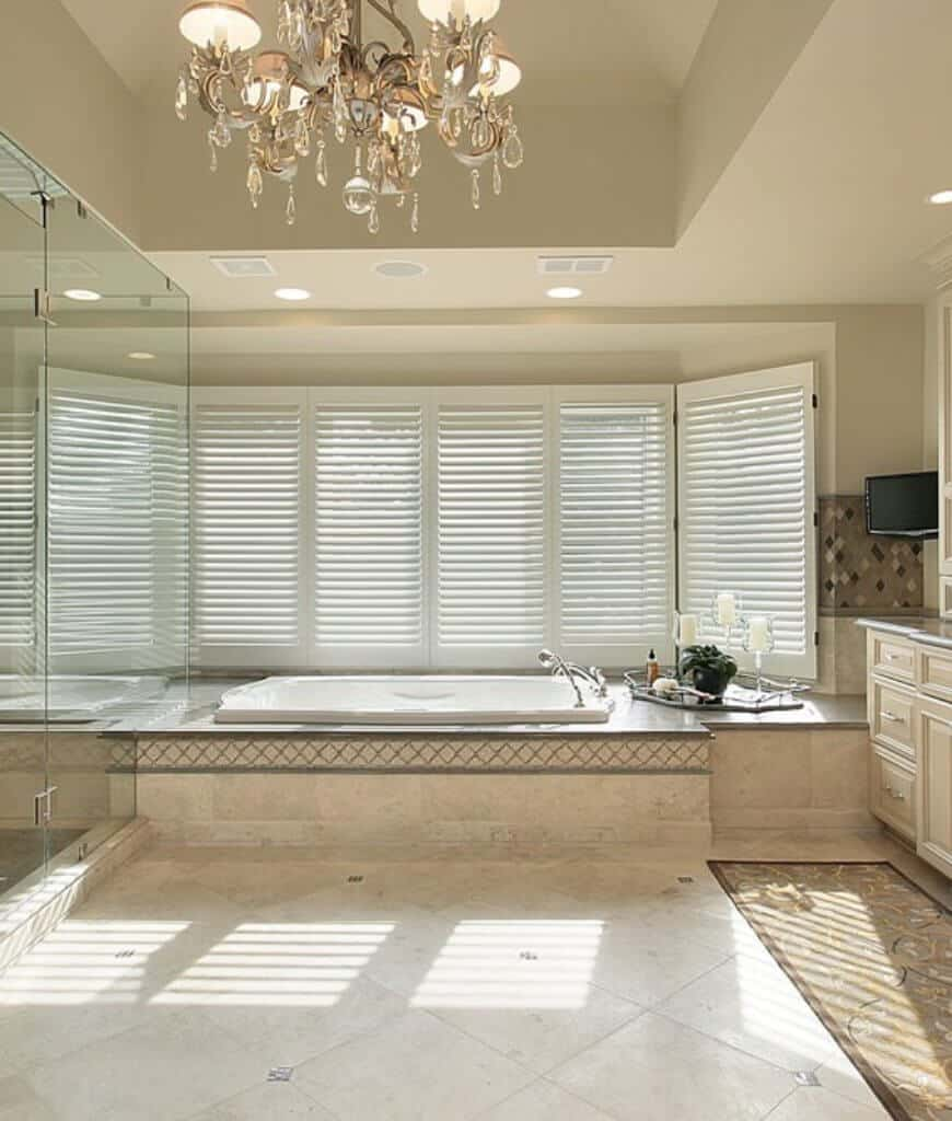 A primary bathroom with a soaking tub and walk-in shower enclosed in frameless glass. It has a louvered window and marble tiled flooring topped by a lovely floral runner.osed in glass. It has a louvered window and marble tiled flooring topped by a lovely floral runner.