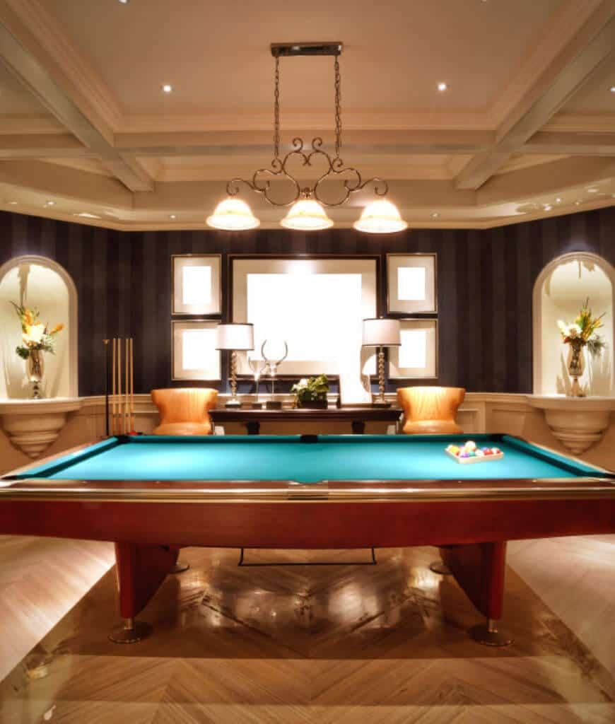 Deluxe game room designed with gallery wall and arched inset niches on the sides fixed above the white wainscoting. It has a pool table across the console desk lighted by table lamps and ornate pendant that hung from the coffered ceiling.