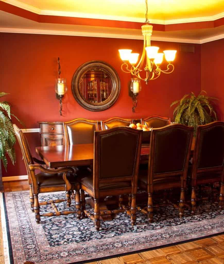 Tropical dining room decorated with a round mirror lighted by wall sconces and a chandelier that hung from the tray ceiling. It has a rectangular dining table and leather chairs over the vintage rug.