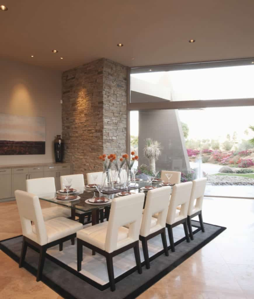 Spacious dining room showcases marble flooring topped by a bordered rug along with a panoramic window overlooking the outdoor yard. It has a glass top dining table surrounded by white modern chairs.