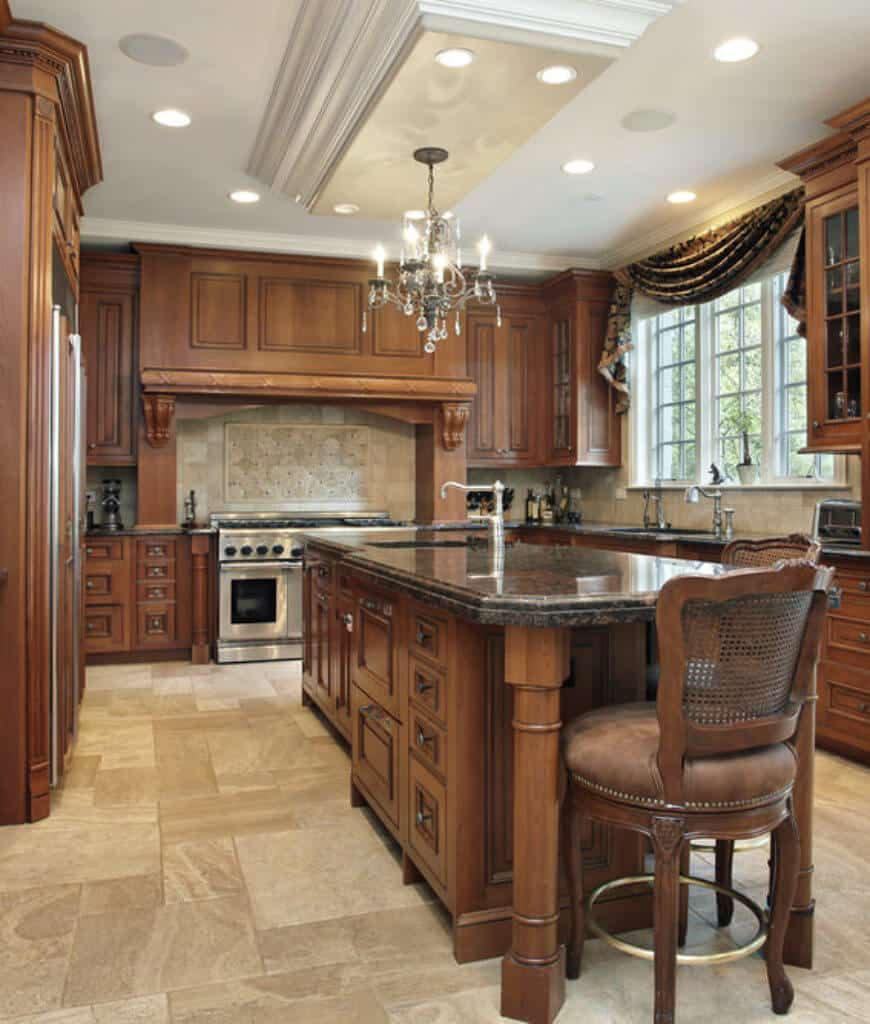 Classic kitchen with a vintage chandelier and central breakfast island surrounded with wooden cabinetry and white framed windows dressed in elegant black valence.