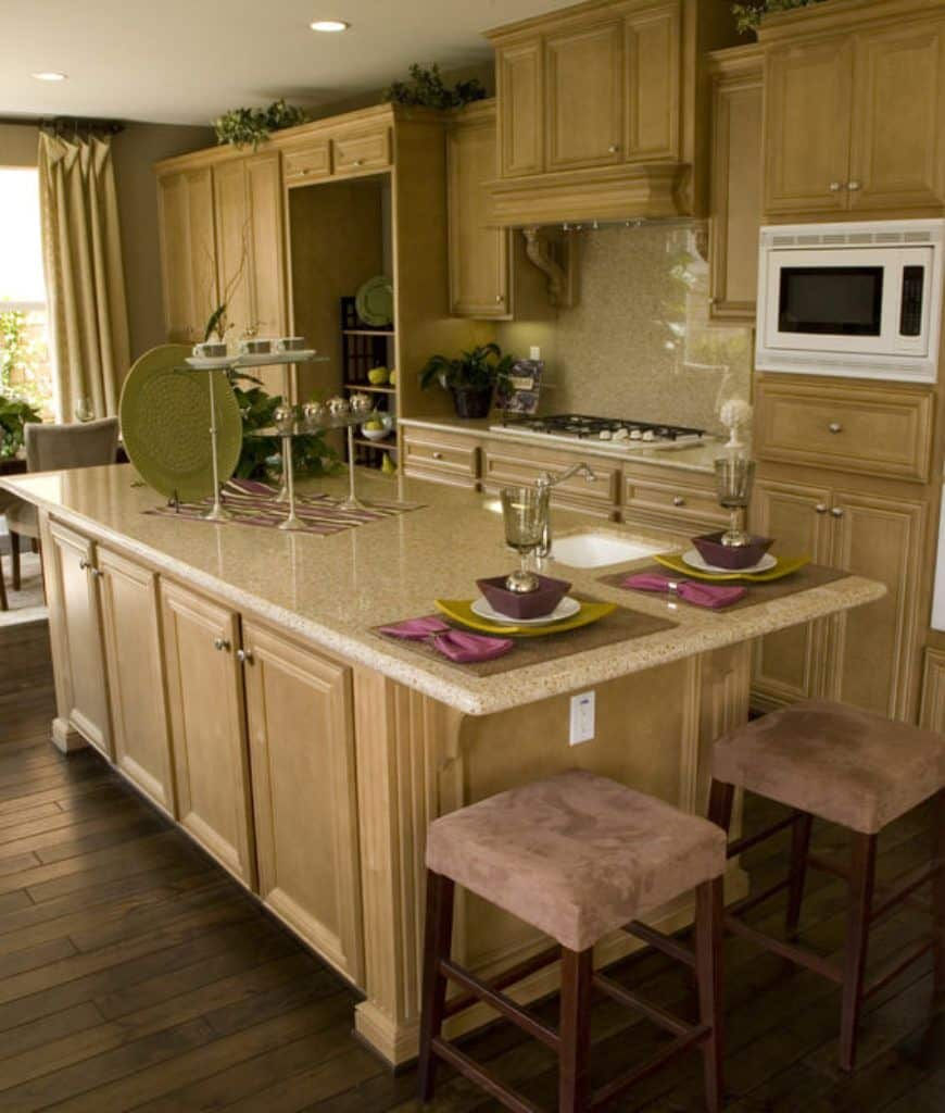 An all wood kitchen offers a white microwave and a kitchen island topped with beige marble counter and paired with brown velvet bar stools.
