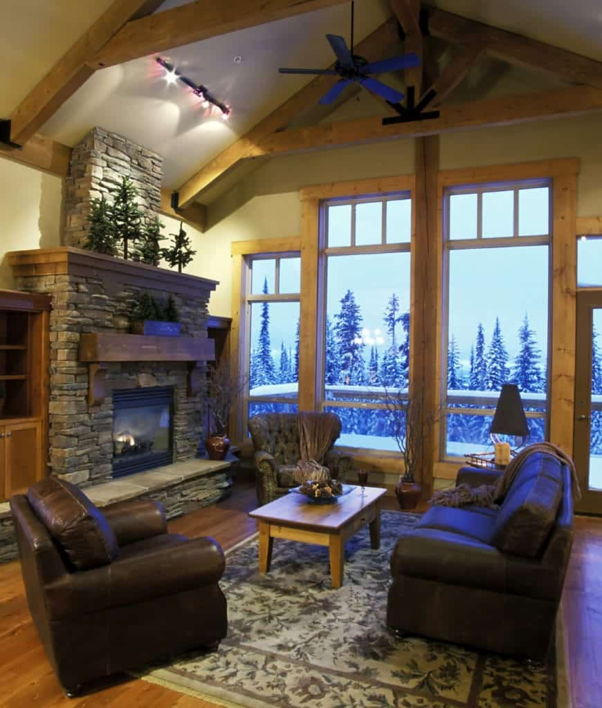 Cozy living room with a stone fireplace lined with a rustic wooden mantel and glass paneled windows that overlook the serene outdoor view.