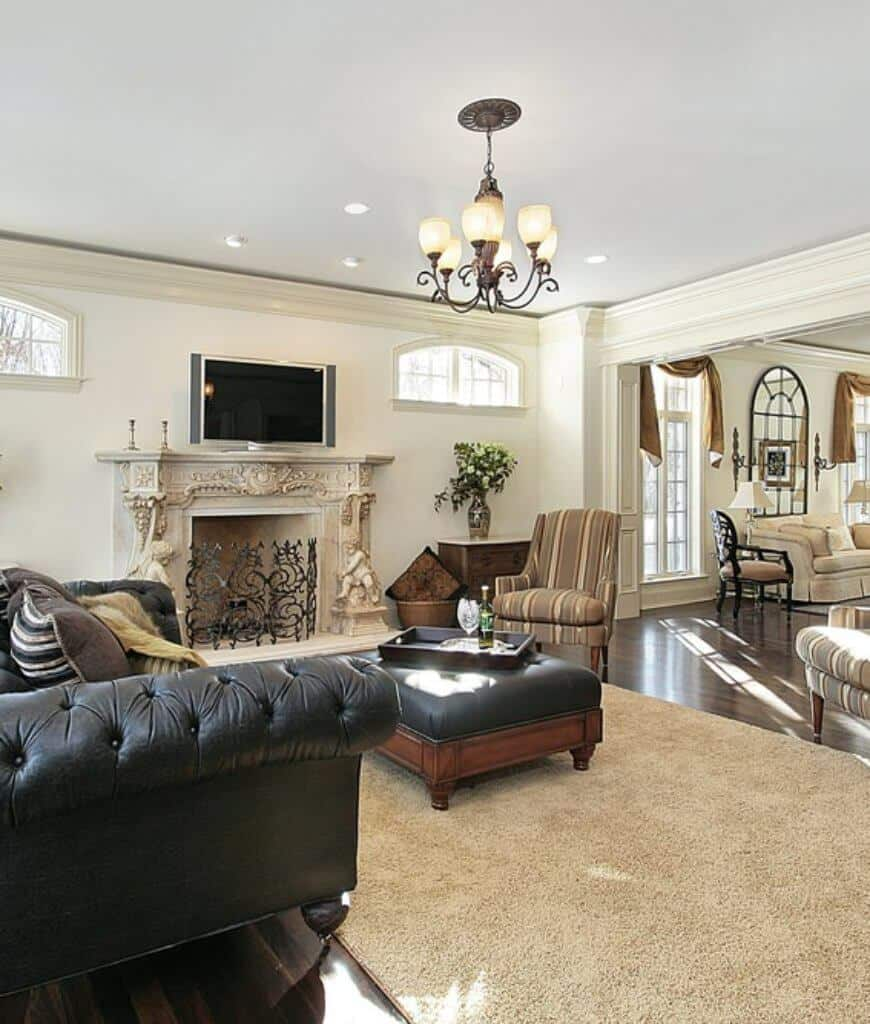 This living room offers striped chairs and a black tufted sofa that matches with the leather ottoman facing the ornate fireplace framed with a wrought iron fence.