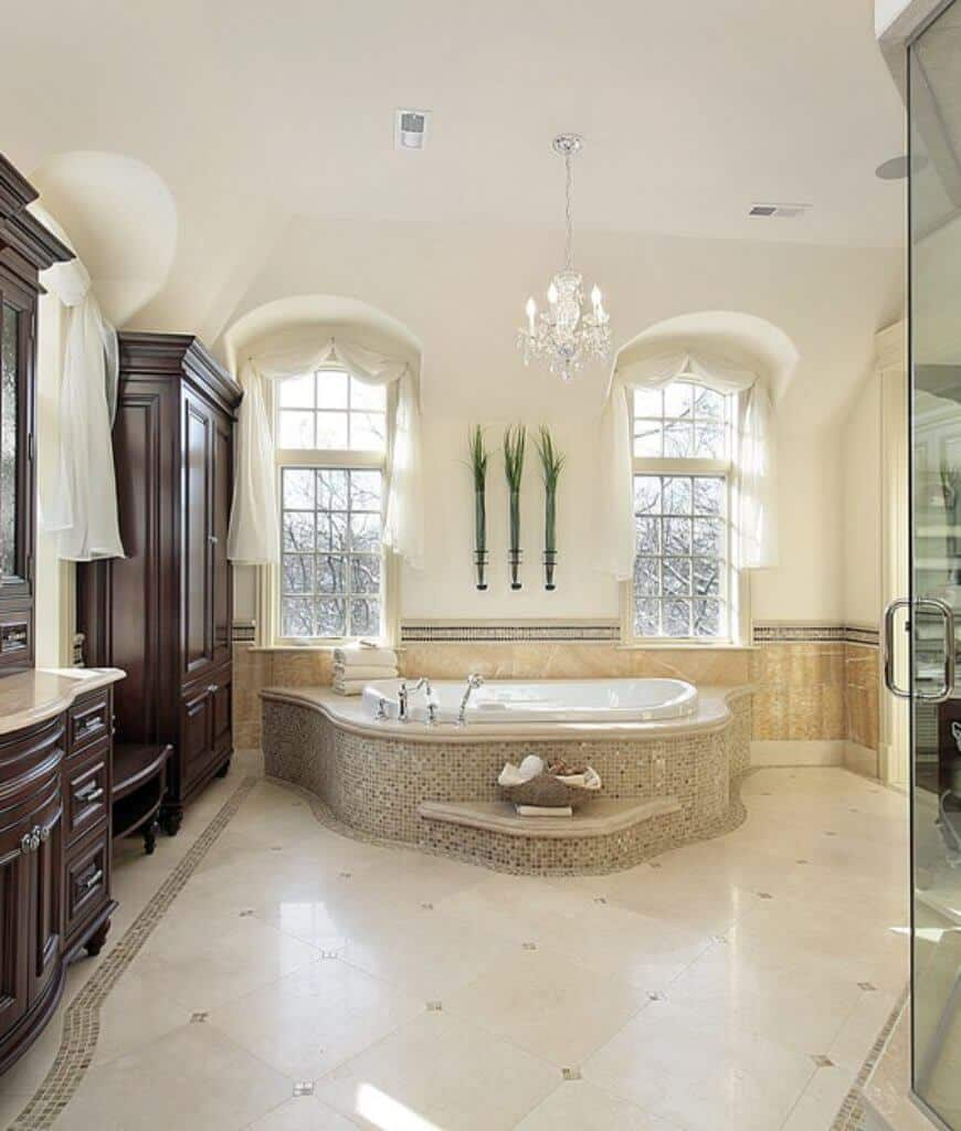 A crystal chandelier illuminates this primary bathroom boasting a drop in bathtub by the glazed windows dressed in white valences.