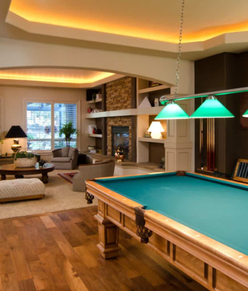 Warm man cave with a pool table in front of the living area filled with comfy seats and a brick fireplace. The low ambient lighting from the strip lights on the tray ceiling gives a warm and cozy vibe to the room.