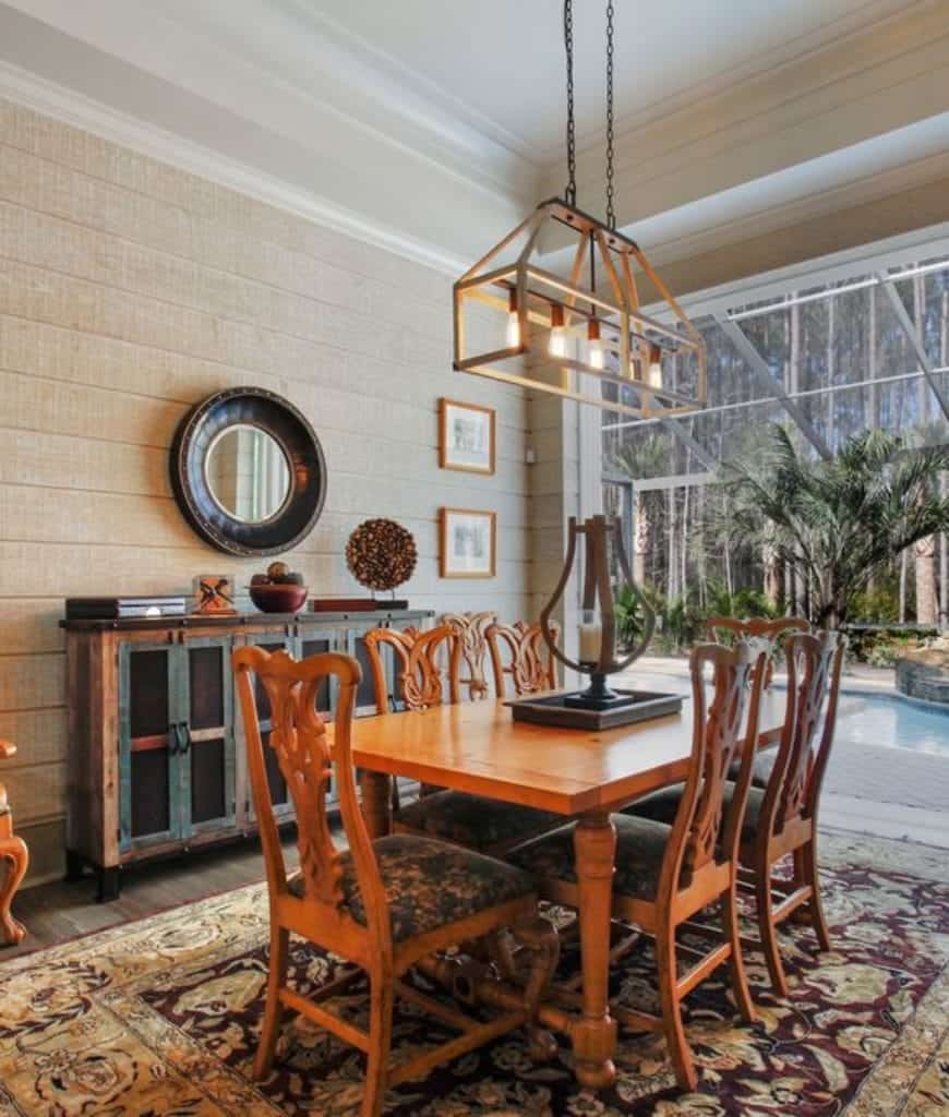 An industrial linear chandelier hangs over the wooden dining set on a floral rug in this dining room designed with wall arts and a round mirror mounted above the rustic console table.