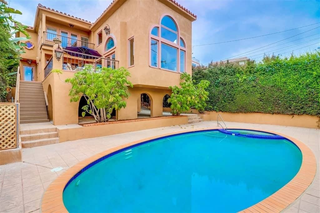 A Spanish home that features balconies and large glass windows that look over a backyard with an oval pool. The earthy tones of the walls, stairs, and stone floor pair well with the abundant greenery of the landscaping. Bluish hues light up the scene from the pool to the several windows that reflect the blue skies.