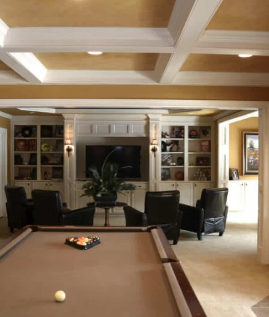 This entertainment room boasts a brown pool table and flat panel TV on a white built-in cabinet surrounded with black leather chairs and open shelving.
