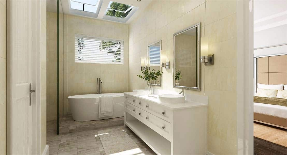 This primary bathroom has beige walls that complement the white vanity and freestanding bathtub at the far end. This bathtub is topped with a window and a couple of sky lights that bring in an abundance of natural lighting.