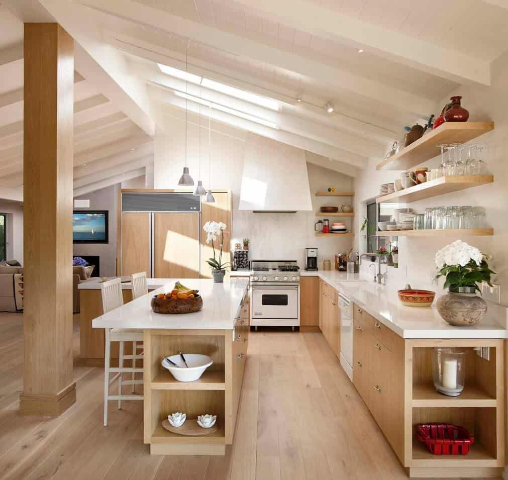 Chrome pendants that hung over the L-shaped breakfast island with built-in shelves and white bar chairs illuminate this kitchen along with skylights fixed to the vaulted ceiling.