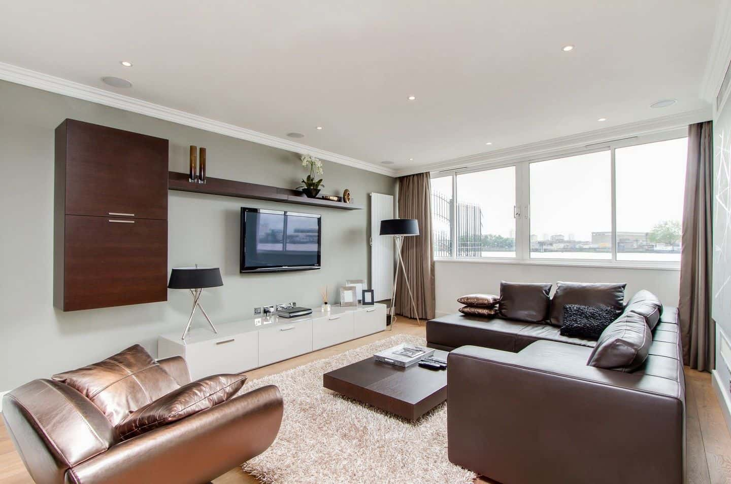 Modern living room furnished with a leather sofa, copper armchair and a low coffee table. It is illuminated by matching floor light and table lamp that sits on the sleek TV stand.