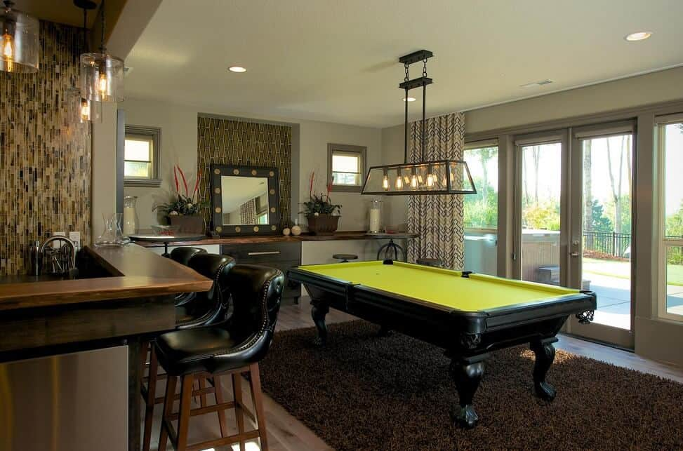 A lime green pool table on a shaggy rug stands out in this transitional family room with a bar and vanity area. It has pendant lights and a French door that leads to the concrete yard.