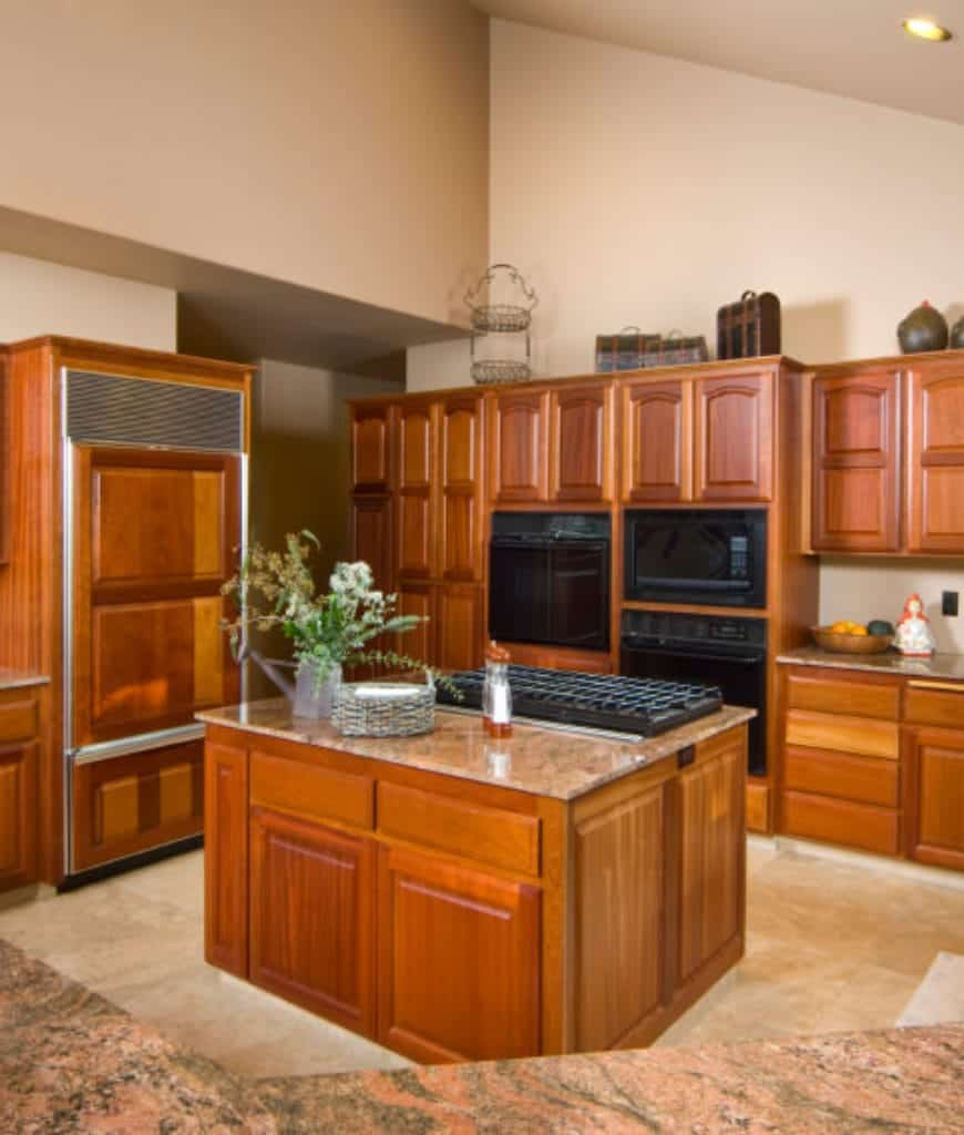 Traditional kitchen offers wooden cabinetry and matching central breakfast island topped with marble counter and built-in cooktop. Beautiful black appliances add modernism to the classic design.