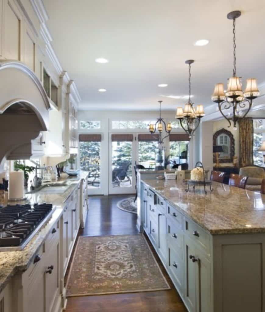 Galley kitchen with glass paneled windows and natural hardwood flooring topped by floral rugs. It has white cabinetry and green breakfast bar lined with glossy counter chairs and shade chandeliers.