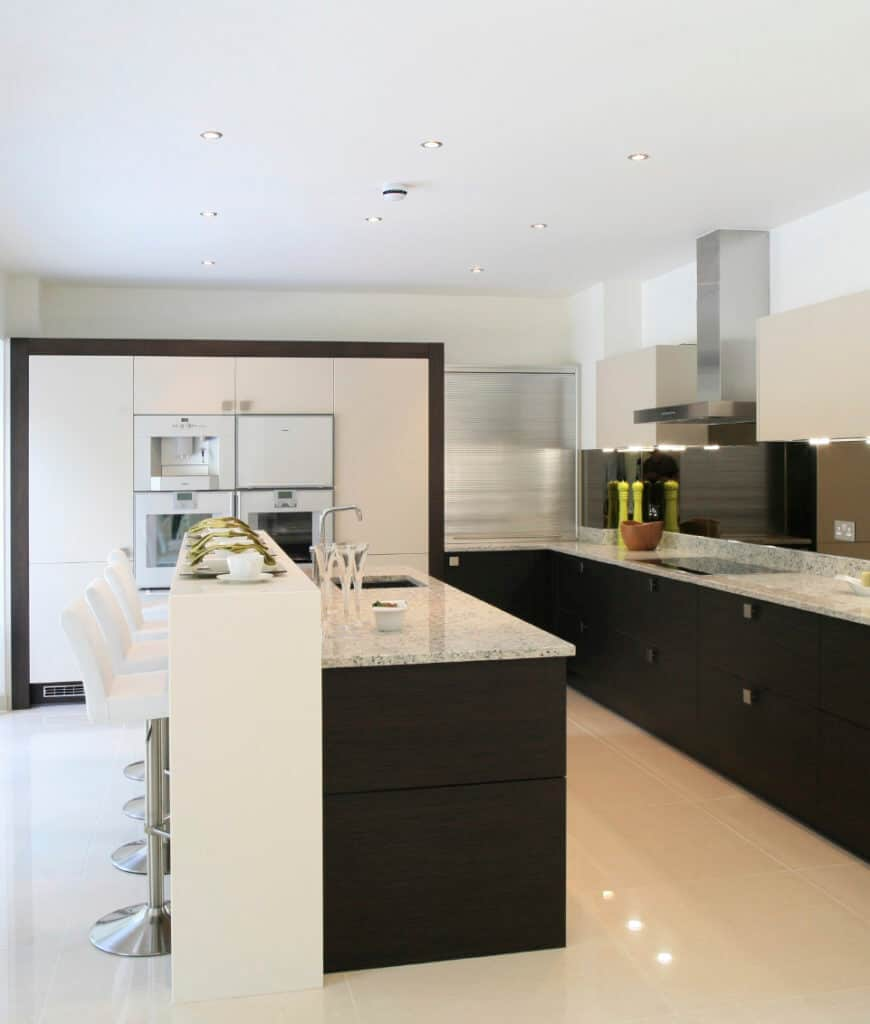 Modern kitchen offers a dark wood two-tier breakfast bar contrasted by white counter stools and cabinetry surrounding the white appliances on the side.
