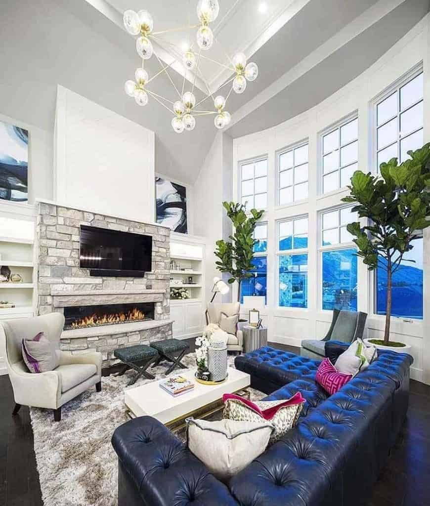 A contemporary chandelier illuminates this living room with black wood plank flooring and white framed windows overlooking a spectacular mountain view.