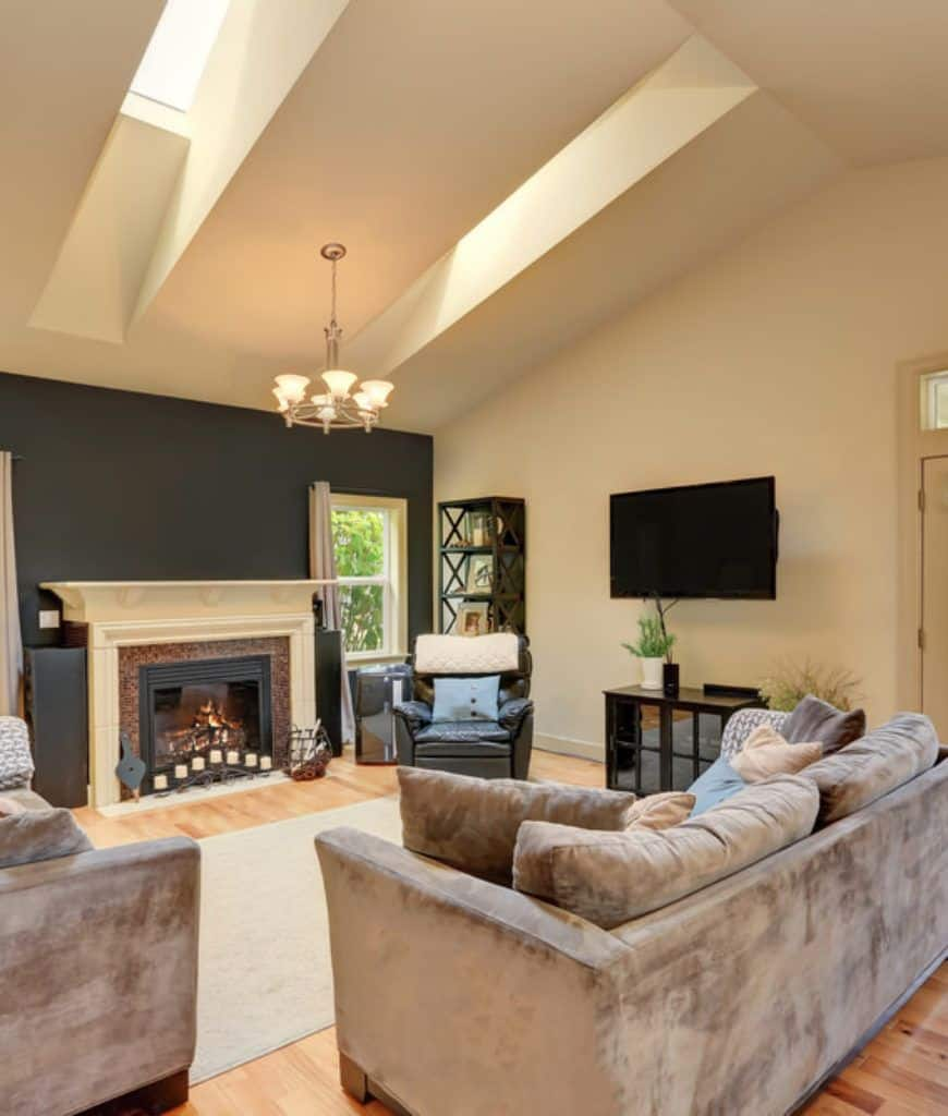 Gorgeous living room boasts a vaulted ceiling with skylights and a hanging chandelier along with black and beige wall mounted with television and fireplace.