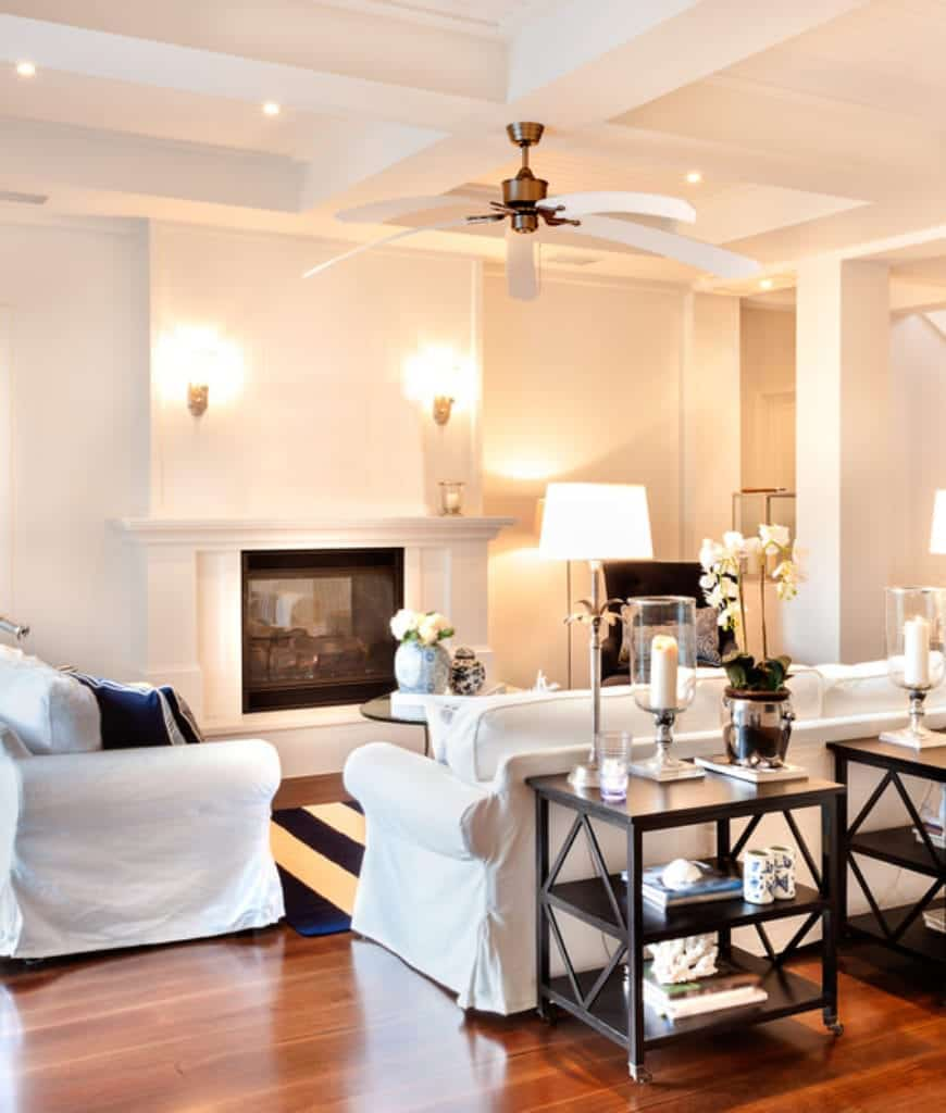 This living room offers a white fireplace lighted by wall sconces and dark wood sofa tables filled with books and candles.
