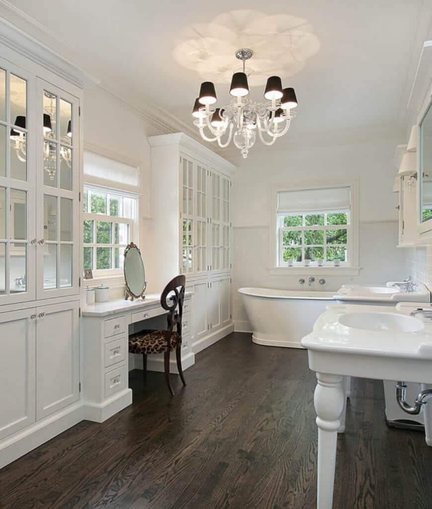 White primary bathroom with double washstand and vanity in between glass front cabinets. It includes a freestanding bathtub by the framed window covered in white roman shade.
