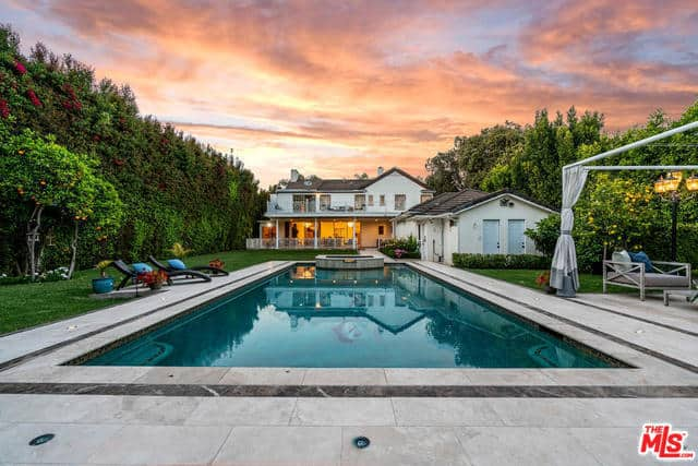 Traditional 2-story home facing a rectangular swimming pool.
