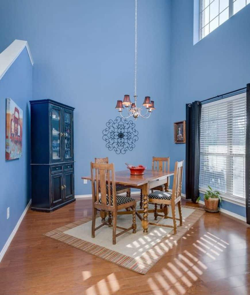 Blue dining room with high ceiling and hardwood flooring topped by a bordered rug. It includes a black display cabinet and wooden dining set on a slant layout.