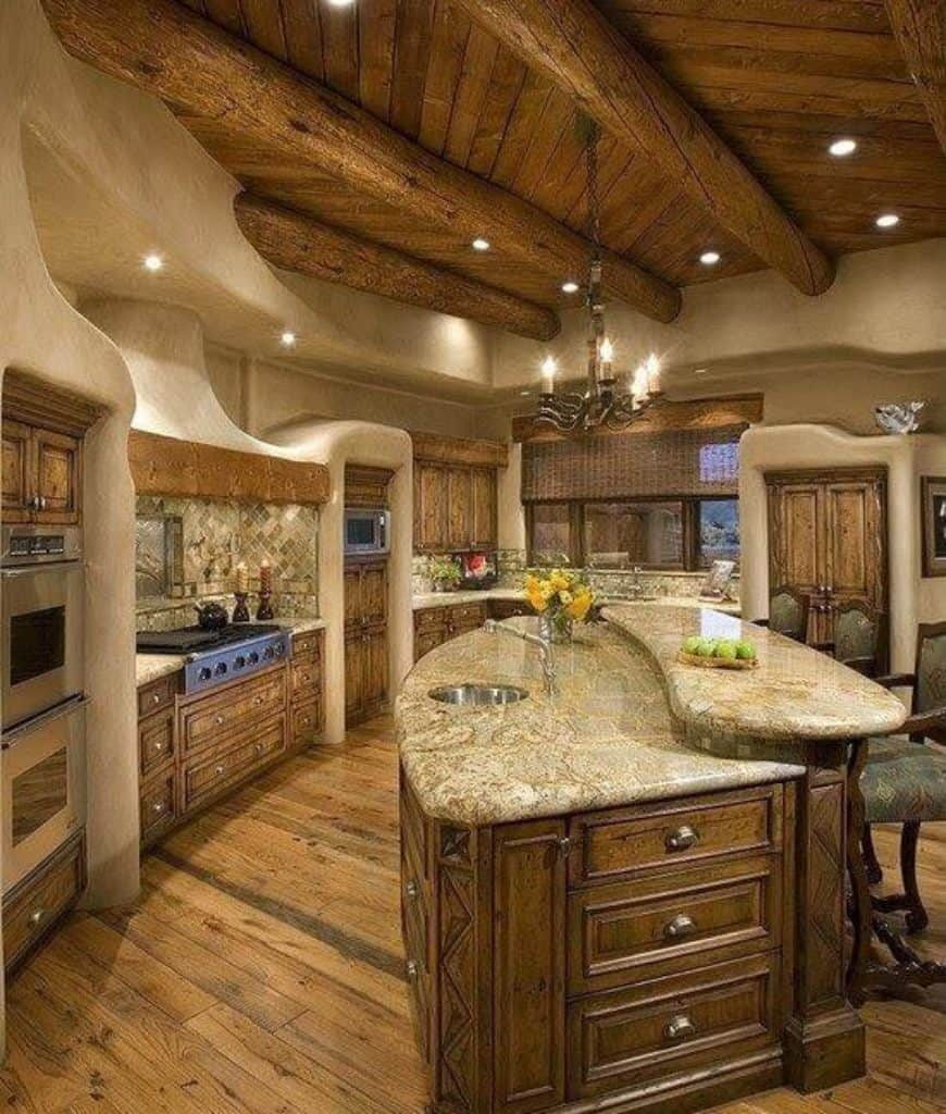 Southwestern kitchen with wood plank flooring and candle chandelier that hung from the wood beam ceiling. It includes a raised central island topped with marble counter and surrounded by natural wood cabinetry.
