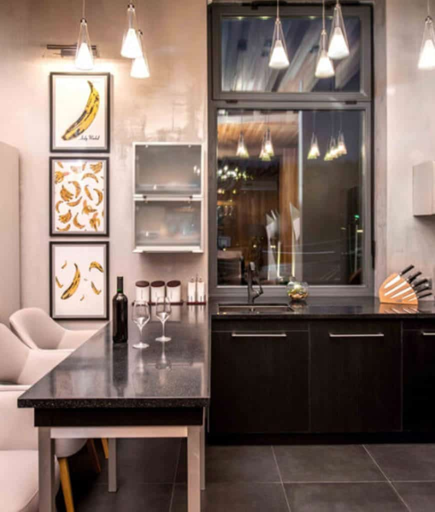 Modern cottage kitchen decorated with lovely wall arts that are mounted next to the frosted glass front cabinets. It has glass pendant lights and granite top peninsula paired with gray counter chairs.