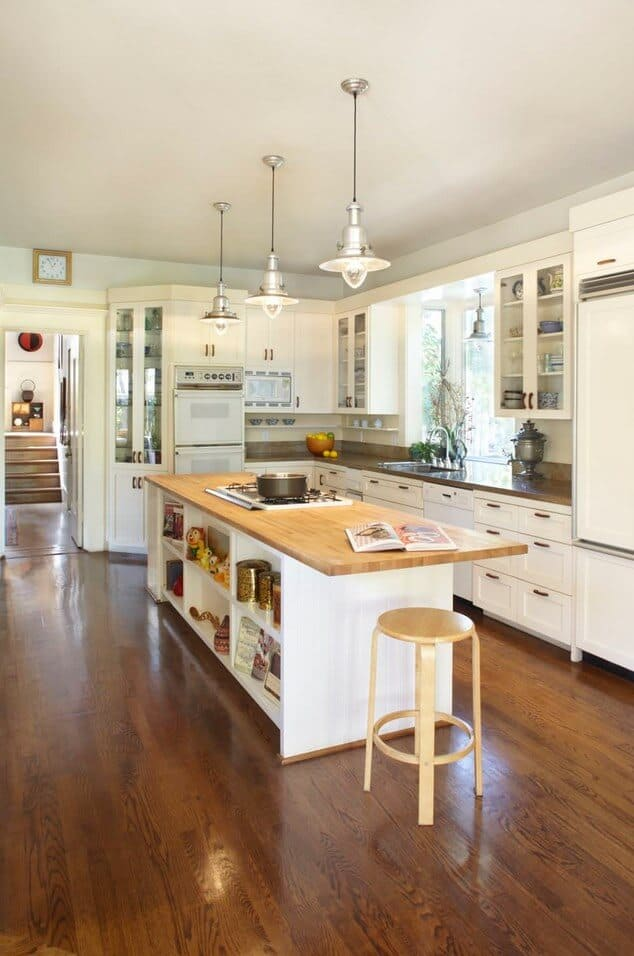 Chrome pendant lights that hung over a kitchen island with built-in shelves topped with a wooden counter and cooktop illuminate this white kitchen showcasing white appliances and cabinetry.