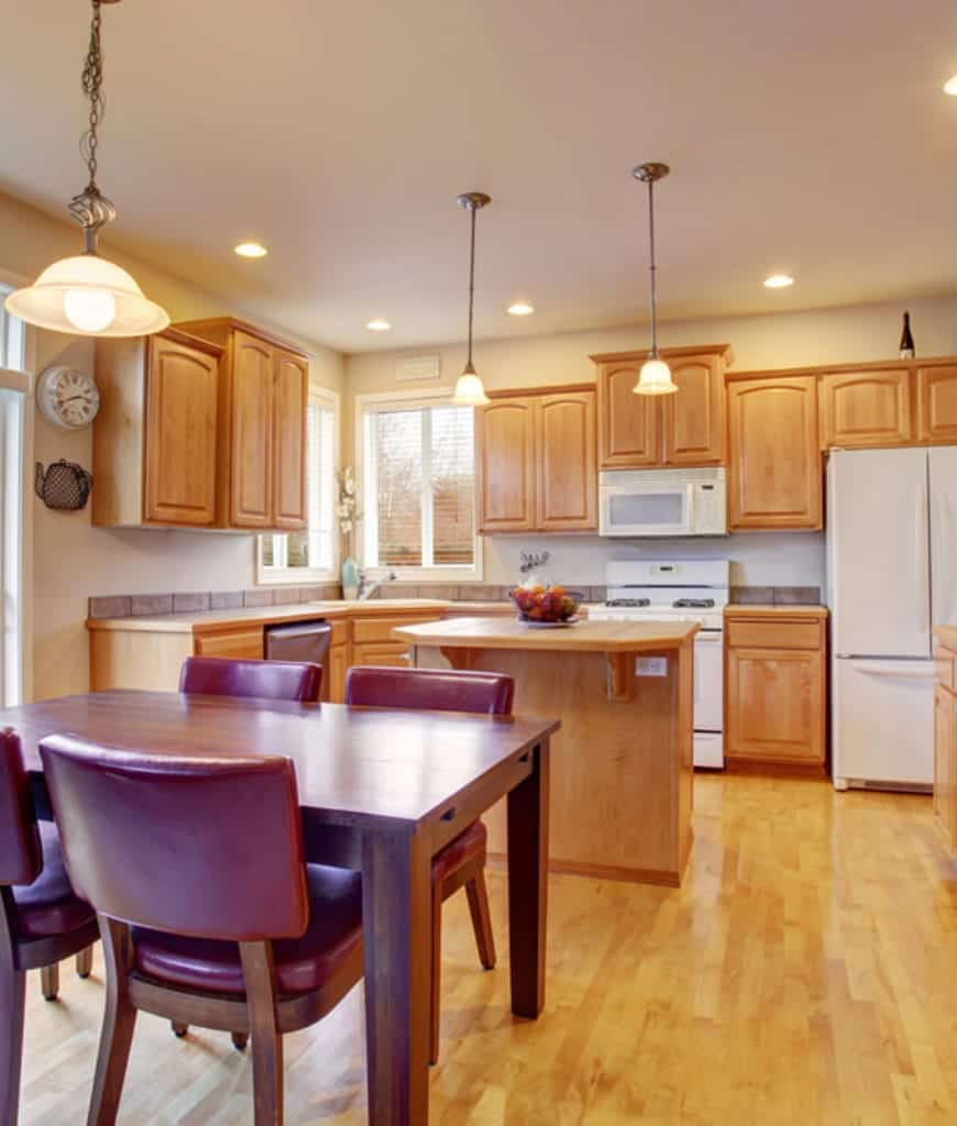 Warm eat-in kitchen with white appliances and light wood cabinetry that blends well with the hardwood flooring for a unified look. It includes dome pendants and a wooden dining table accompanied by red leather chairs.