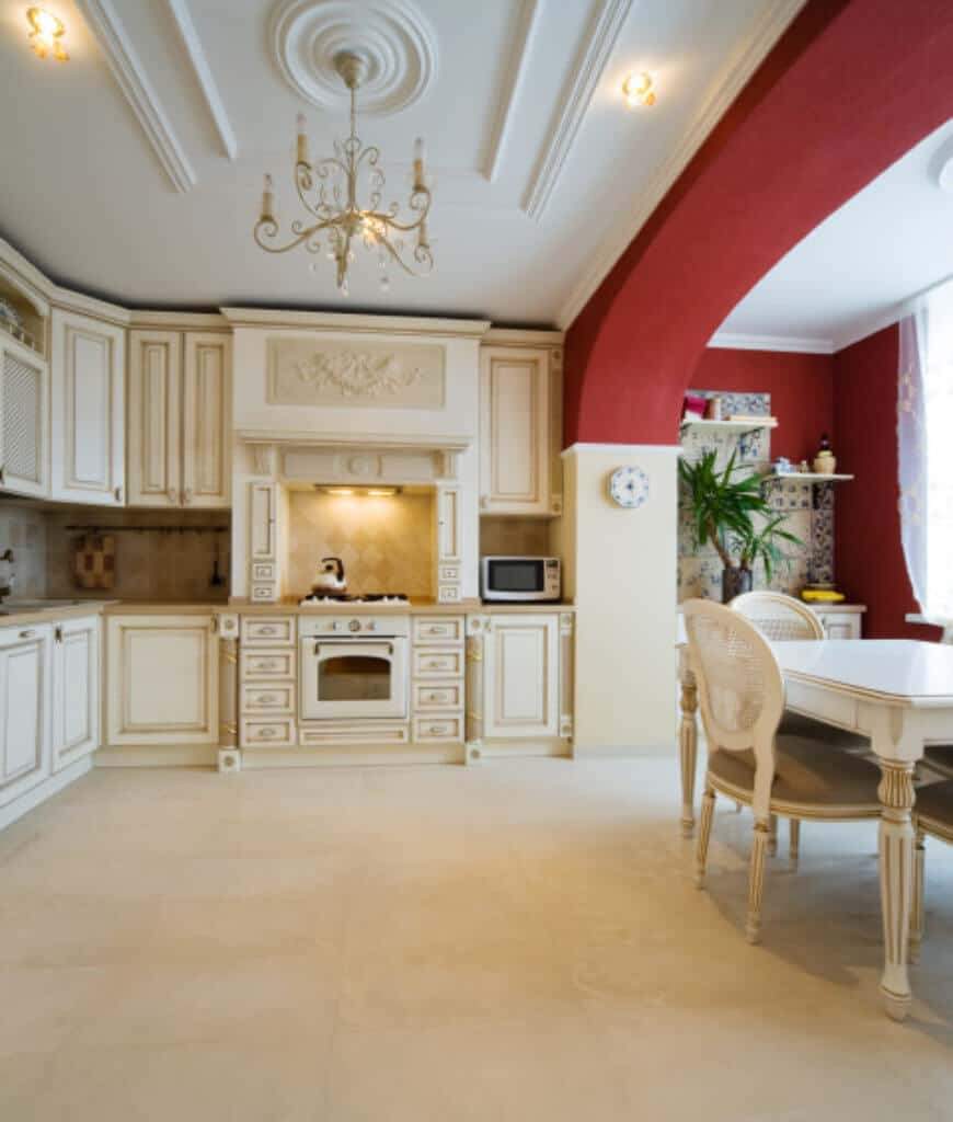 Spacious eat-in kitchen with white ornate cabinetry and appliances accented with red walls on the dining space area. It is illuminated by a fancy chandelier that hung from the tray ceiling.