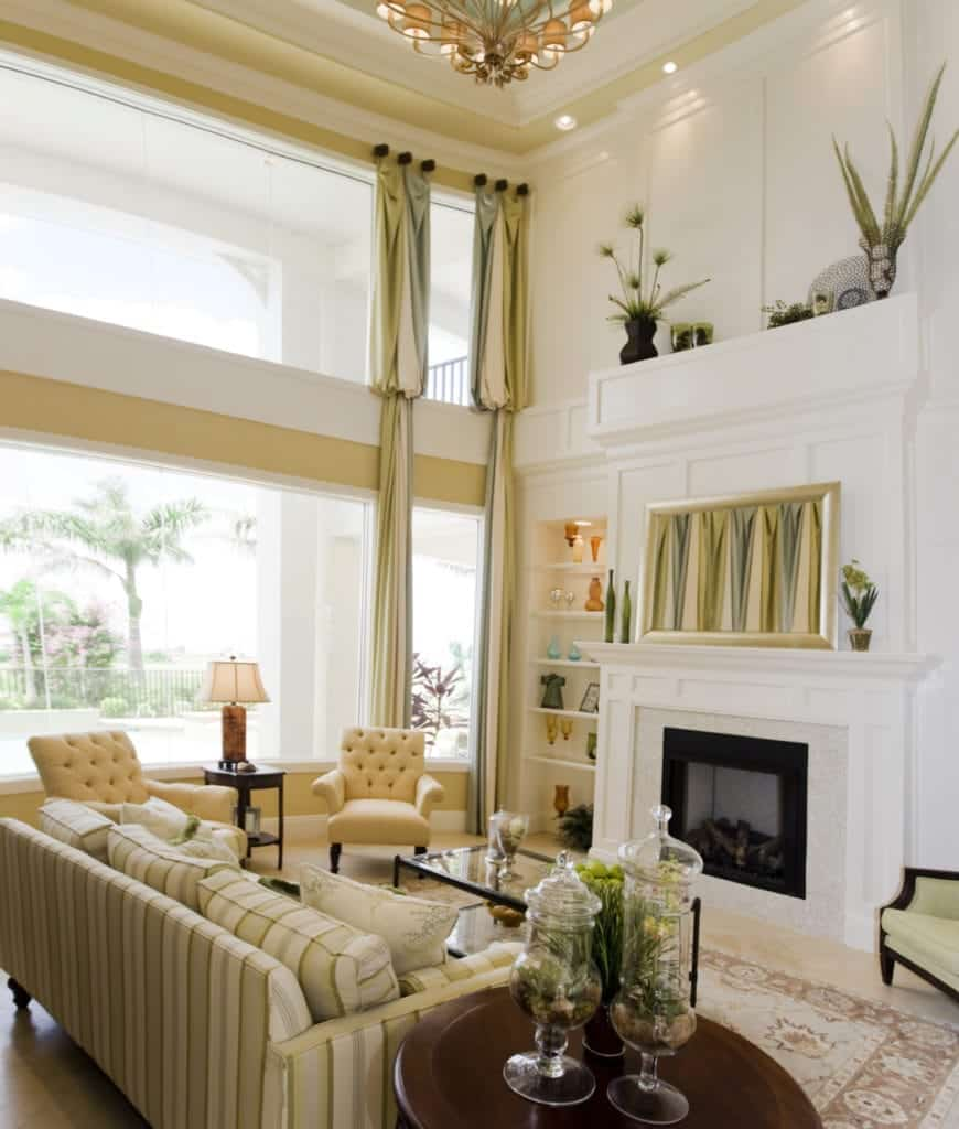 Bright living room with tufted armchairs and a striped sofa that complements with the wall art above the fireplace and draperies on the panoramic windows.