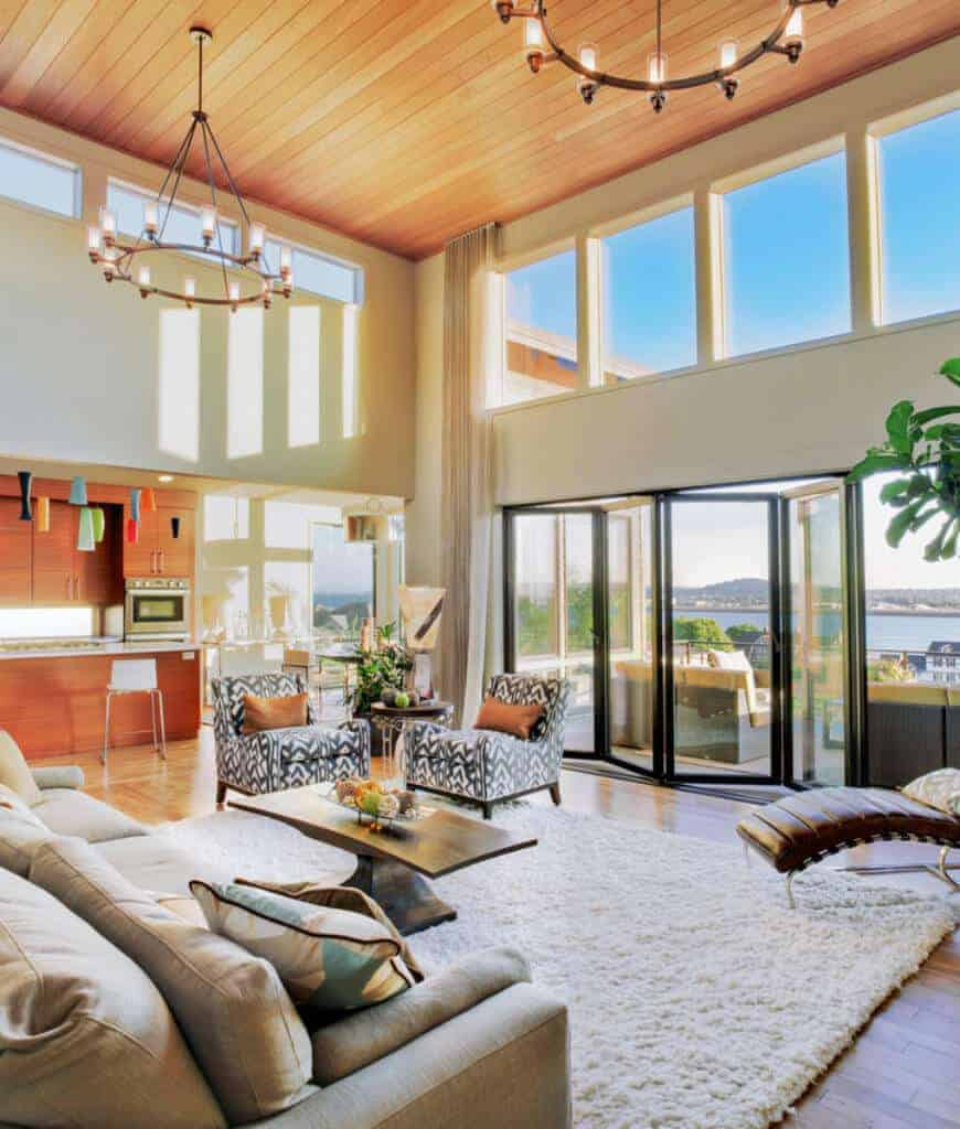 An open living room with wooden coffee table and cozy seats over a beige shaggy rug. It has wood plank flooring and folding glass door that opens to the balcony with an amazing ocean view.