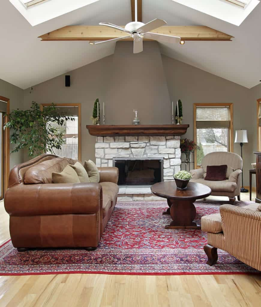 Gray living room boasts a stone fireplace lined with wooden mantel that complements with the round coffee table surrounded with a leather sofa along with round back and striped armchairs.