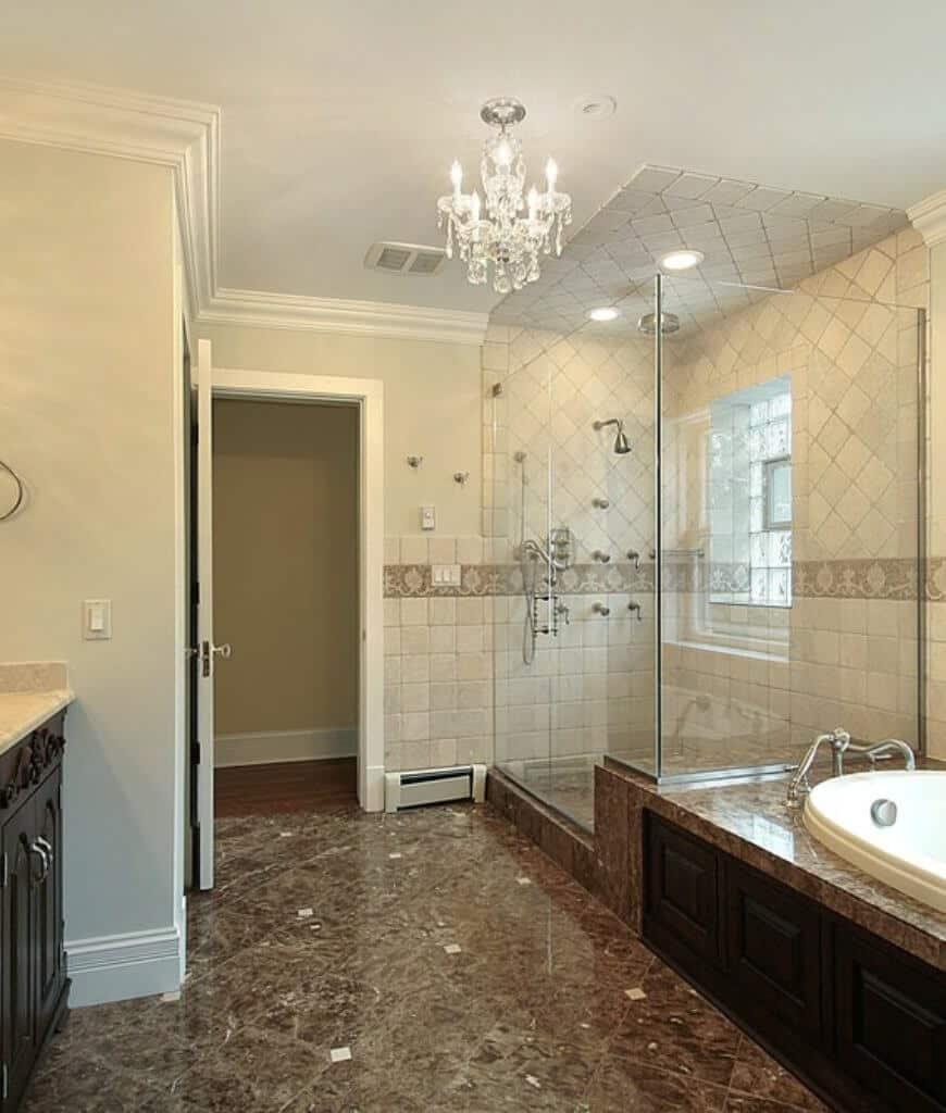 This primary bathroom features a soaking bathtub that sits beside the walk-in shower. You can feel its elegance from the marble flooring and crystal chandelier.