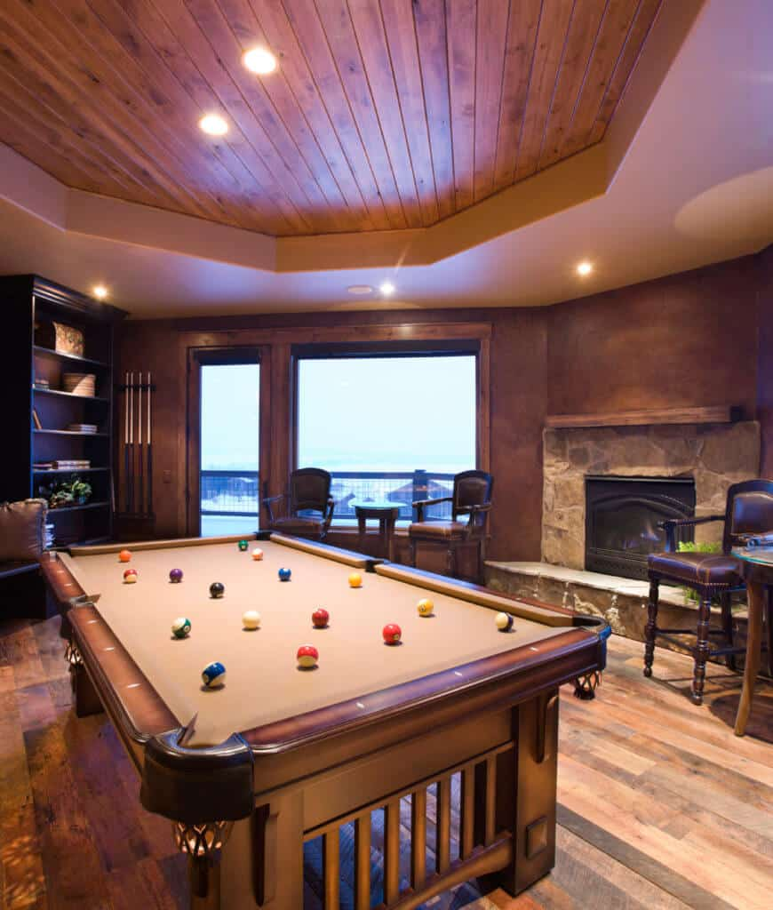 Rustic man cave showcases black shelving and a stone fireplace along with a pool table beneath the tray ceiling clad in wood planks.