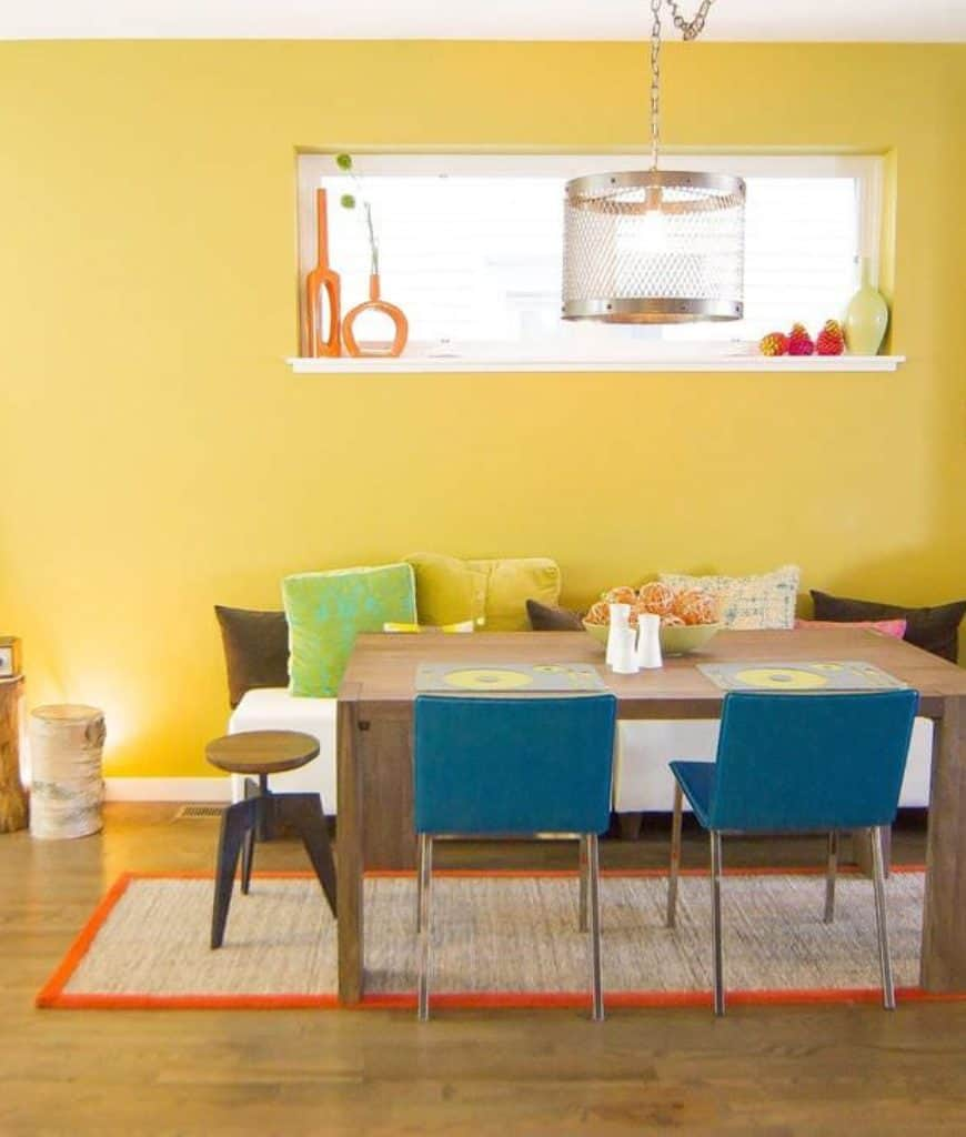 Yellow dining room illuminated by a perforated pendant light that hung over the rustic dining table surrounded with round and blue chairs along with a white bench filled with bright pillows.