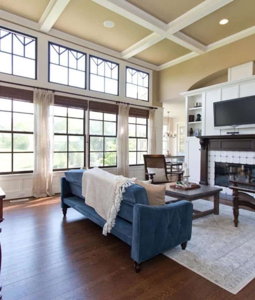 An airy living room with beige coffered ceiling and framed windows bringing plenty of natural light in. There's a blue sofa in the middle facing the fireplace fixed to the white wall panel with built-in shelving.