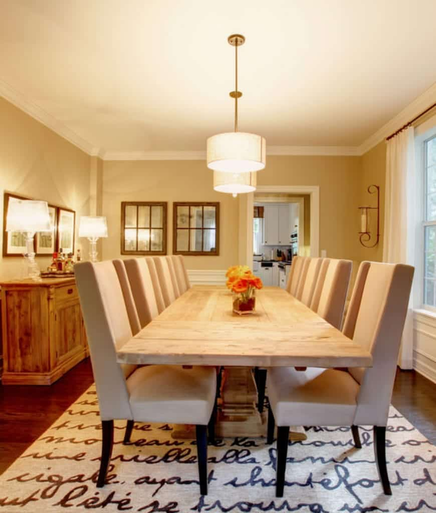 This dining room features a beige area rug with black writing and a light wood dining table paired with high back chairs. There's a buffet table on the side topped with glass table lamps.