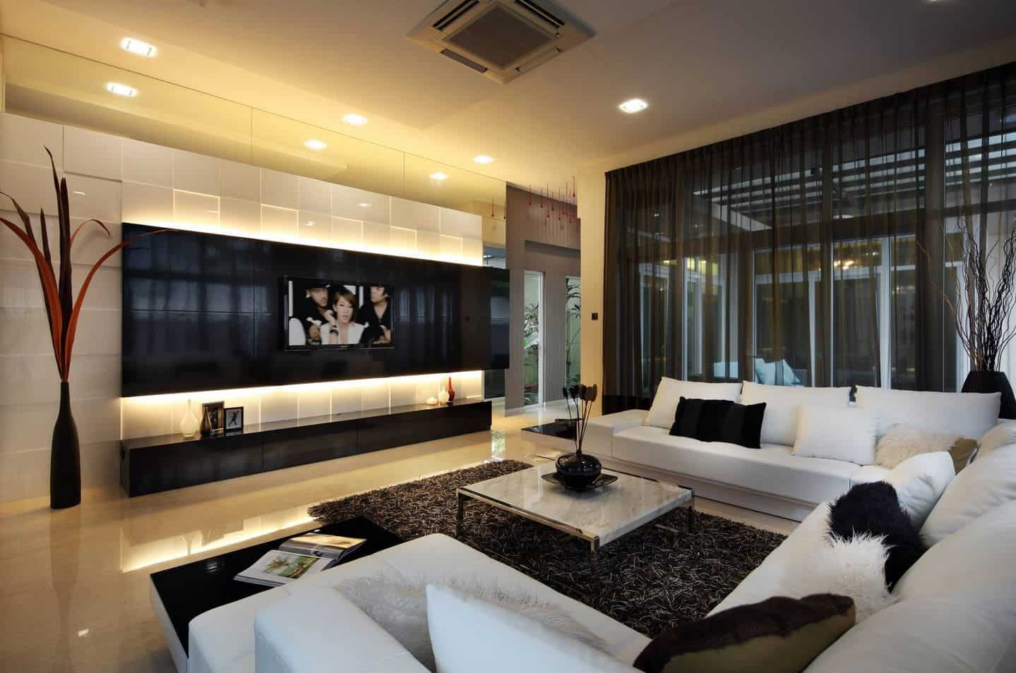 Modern living room with a gray sofa and marble coffee table facing the television that's fixed to the black panel. It has glossy tiled flooring and full height glazing covered with black sheer curtains.