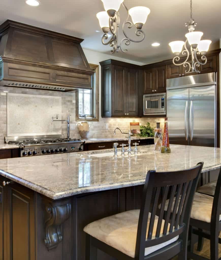 Beige cushioned chairs sit at a dark wood breakfast island in this kitchen with wooden cabinetry and ornate chandeliers.