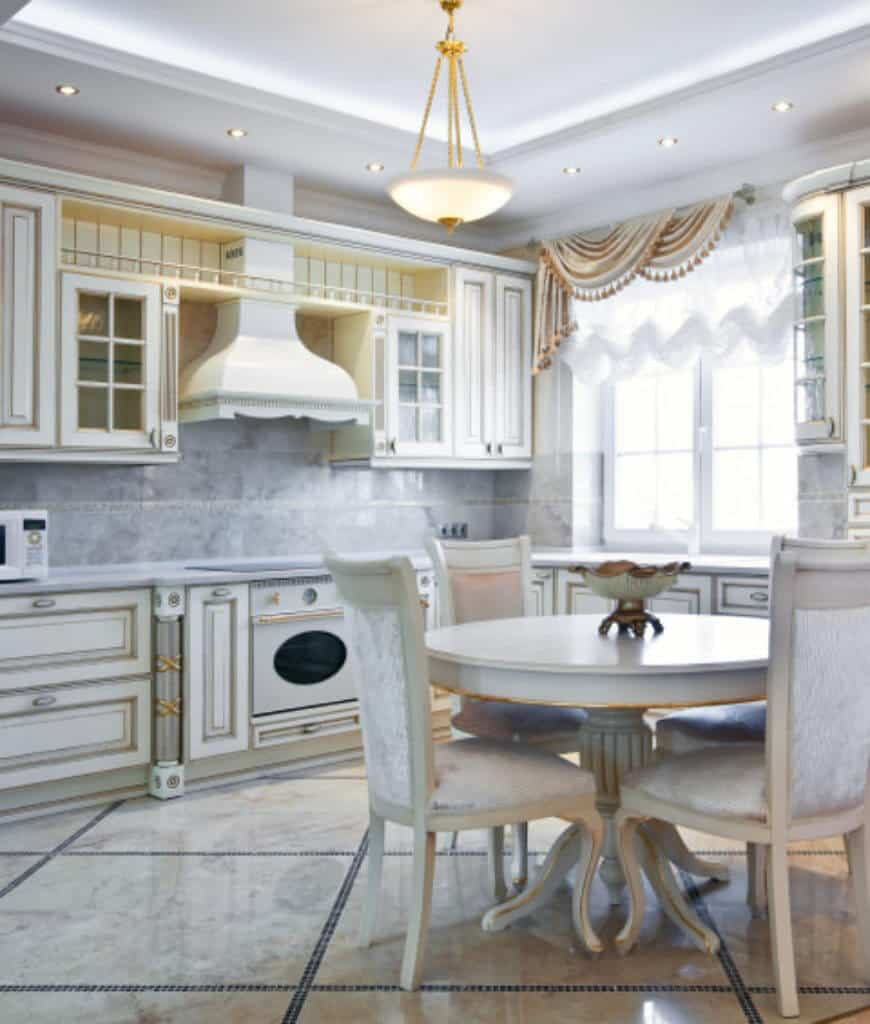 Marbled kitchen features glass windows covered in classy valences and tray ceiling with a hanging brass pendant light. It has white cabinetry and appliances along with a round dining table surrounded with white velvet chairs.