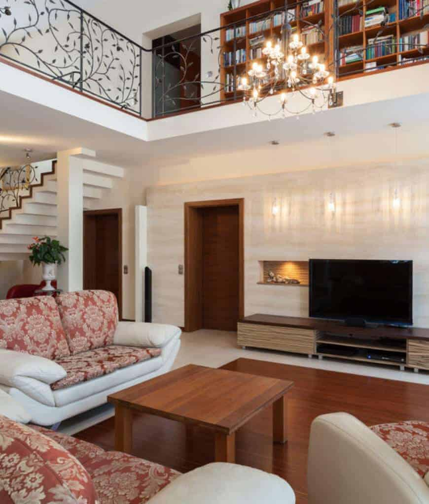 A crystal chandelier illuminates this living room featuring white leather seats fitted with red floral cushions along with a wooden coffee table that complements with the hardwood flooring bordered with white tiles.