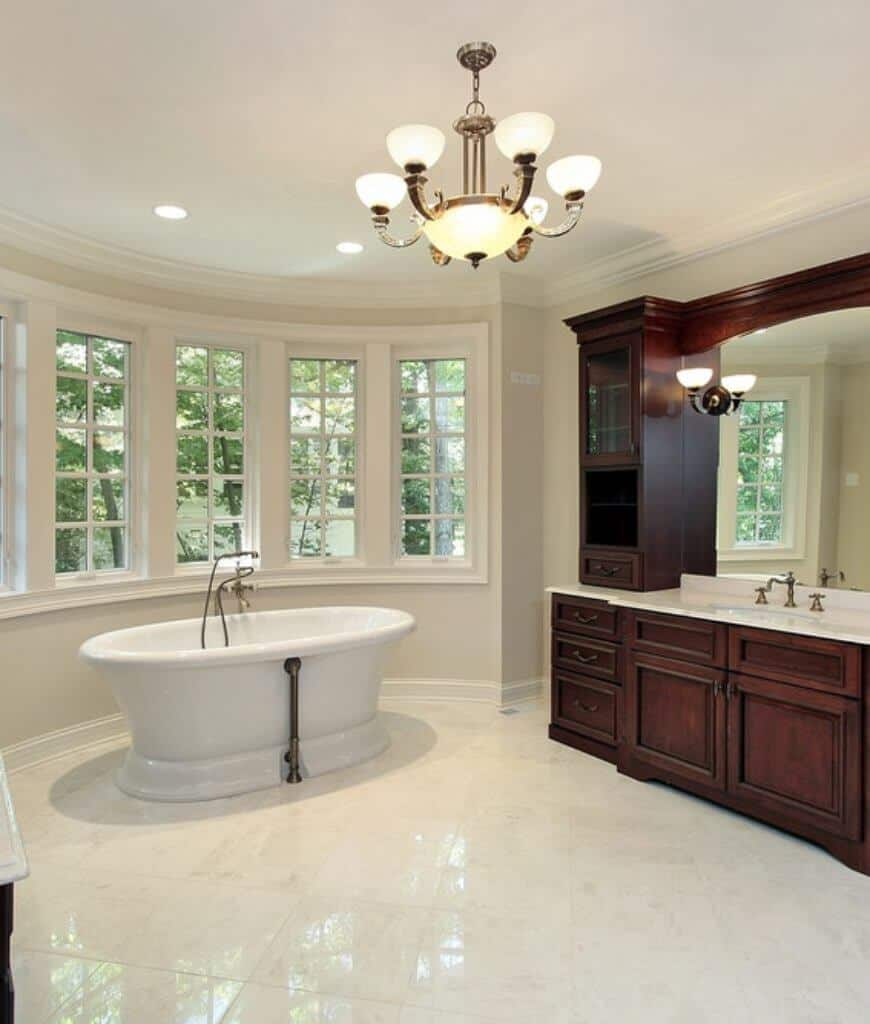 Classic primary bathroom filled with a wooden sink vanity and freestanding bathtub along with a charming chandelier that illuminates the area.
