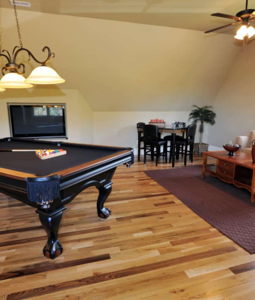 Yellow basement boasts a black pool table that complements with the leather chairs on the side. It has vaulted ceiling and wood plank flooring topped with a textured area rug.