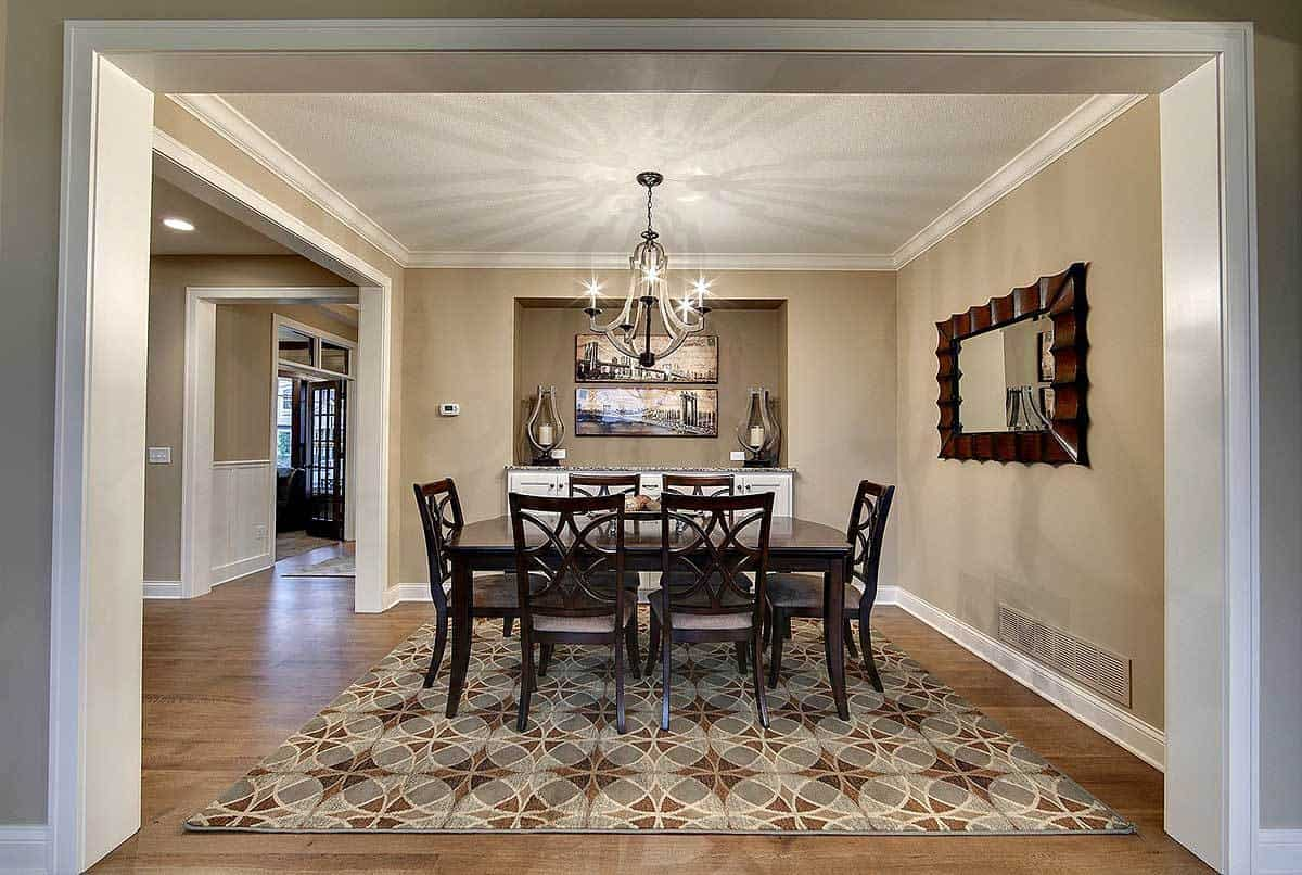 This formal dining area has light gray walls that matches with the patterned gray area rug on the hardwood flooring. These are all contrasted by the dark wooden dining set that matches with the decorative frame of the wall-mounted mirror on the side.