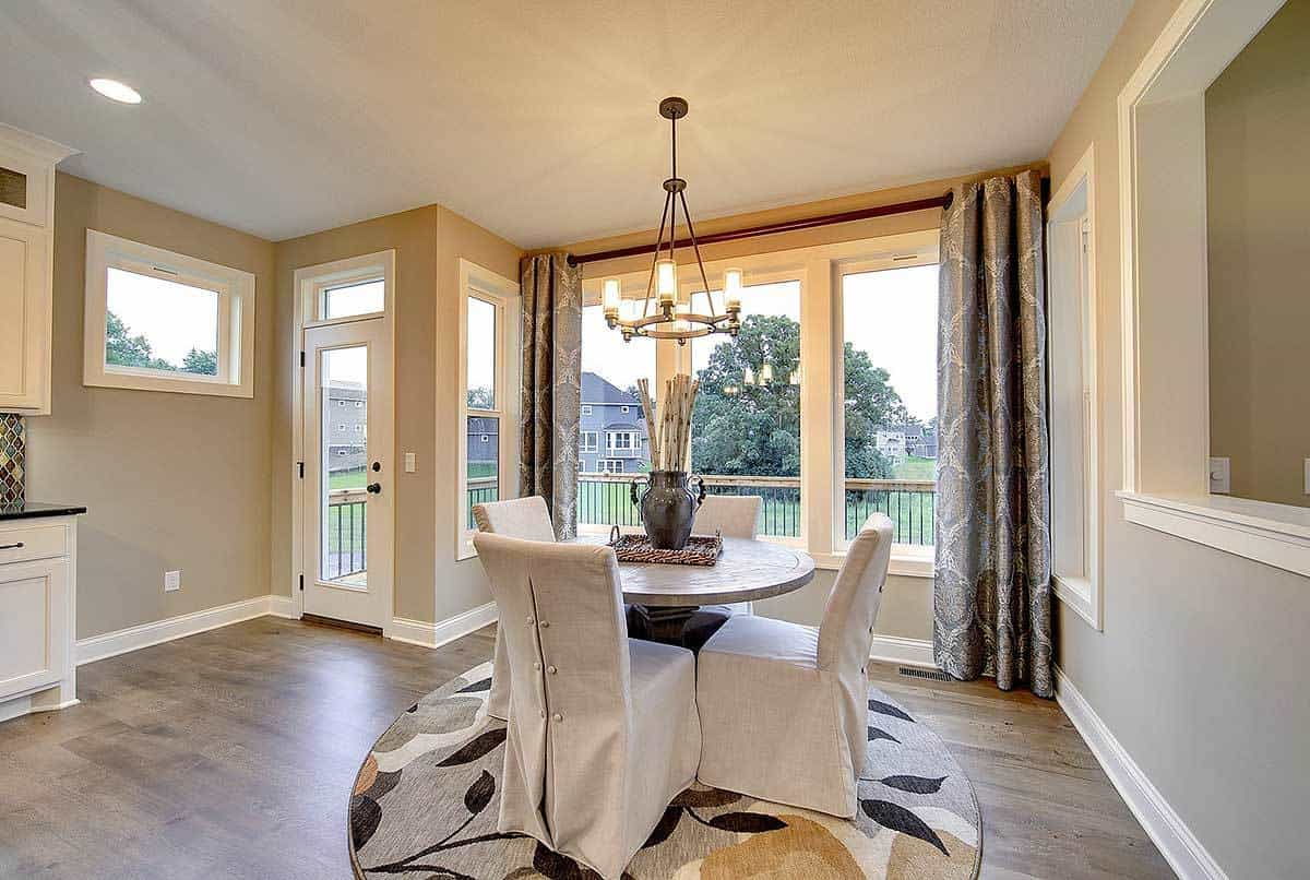 This is an informal dining area beside the kitchen and living room. It has a round wooden dining table surrounded by chairs that have white slipcovers. These are complemented by the small chandelier, surrounding glass windows and chic area rug.