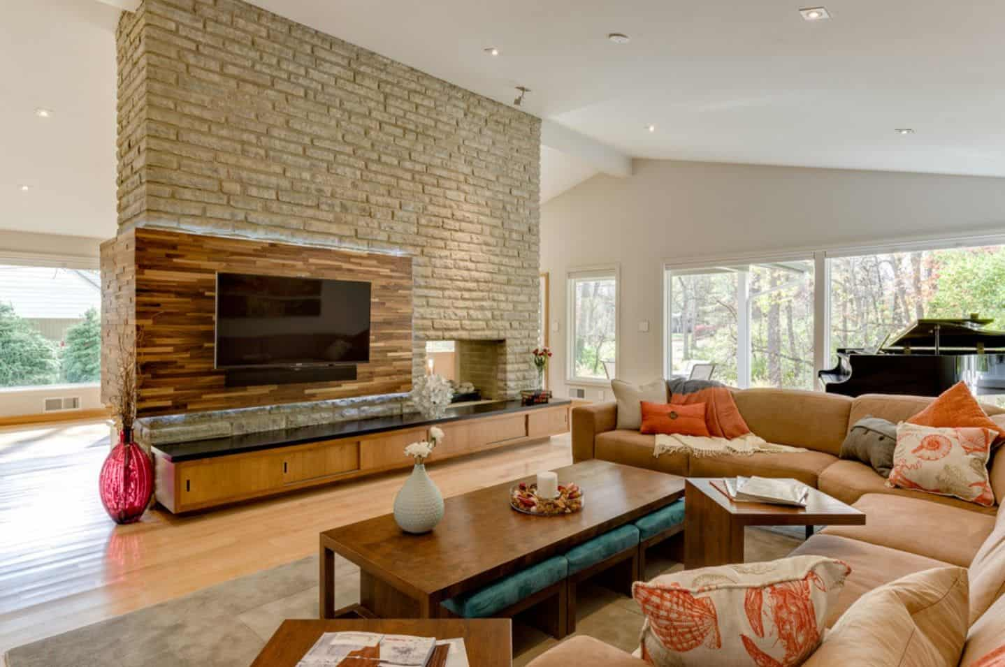 This living room showcases a television and fireplace that's fitted on the stone brick wall. It has coral sectionals and a wooden coffee table with teal stools underneath.