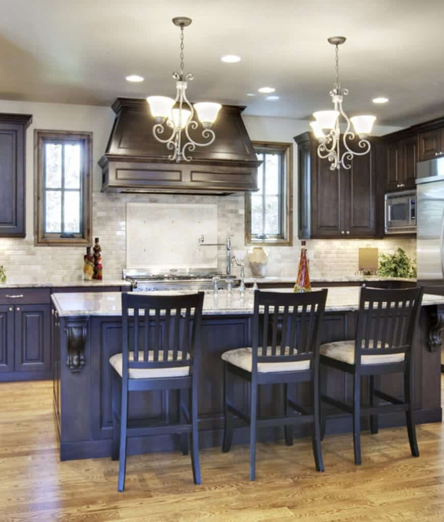 A pair of ornate chandeliers hang over the black breakfast bar lined with matching chairs and topped with a gray marble counter that complements with the subway tile backsplash.