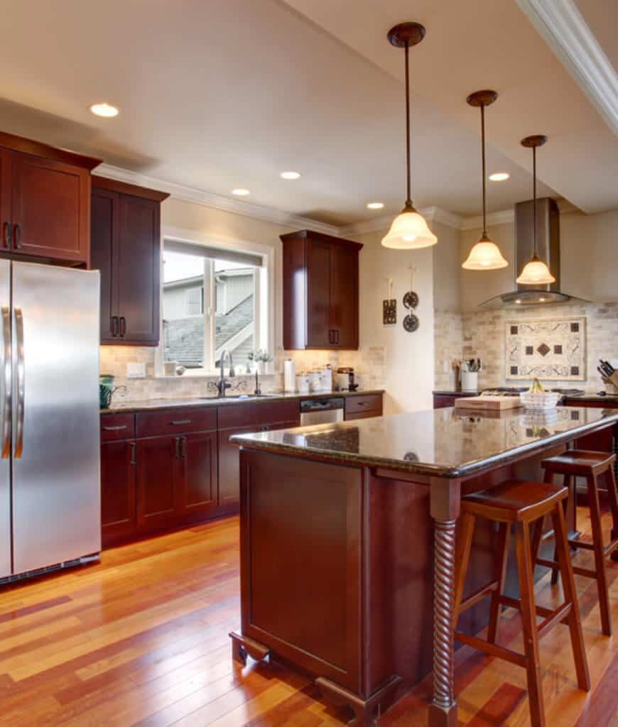 This kitchen showcases redwood cabinetry and a breakfast bar over rich wood plank flooring lighted by glass pendants.